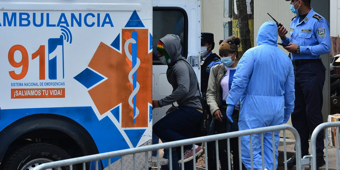 Hondurans who entered the country in the last hours are escorted by authorities as they enter an ambulance to be put in quarantine at the Jose Simon Azcona sports complex to prevent the spread of the new coronavirus in Tegucigalpa on March 18, 2020. (Photo by ORLANDO SIERRA / AFP)